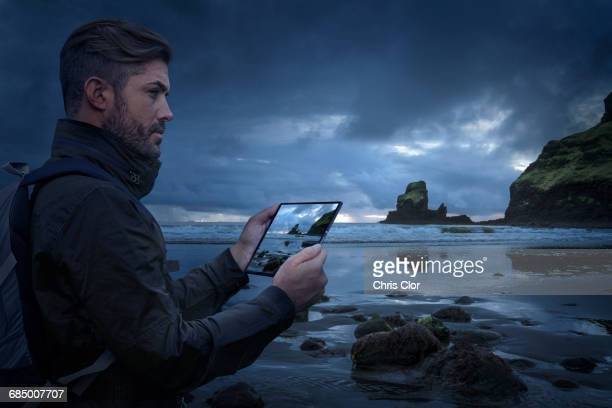 Caucasian hiker photographing beach with digital tablet at sunset