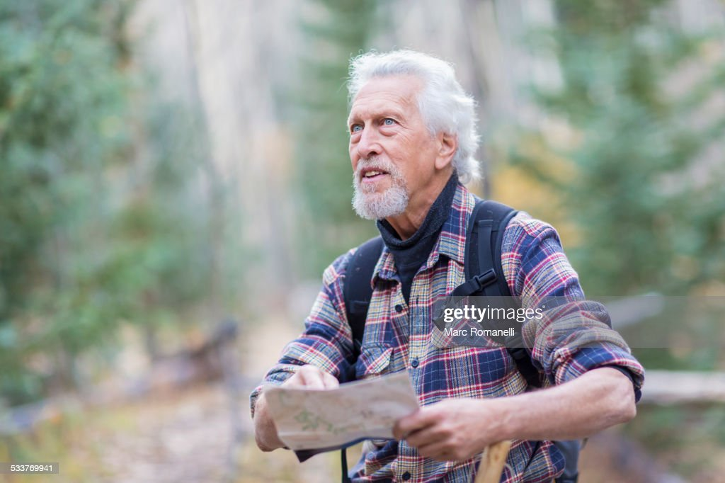 Caucasian hiker reading map in forest : Foto stock