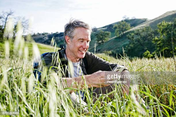 Caucasian hiker sitting in tall grass using cell phone