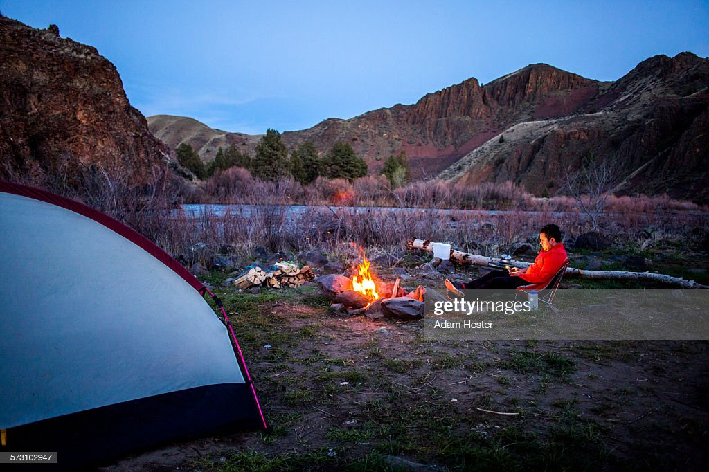 Caucasian hiker sitting near campfire in desert field, Painted Hills, Oregon, United States : Stock Photo