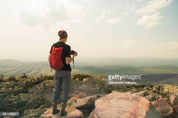 Caucasian hiker standing on rocky hilltop