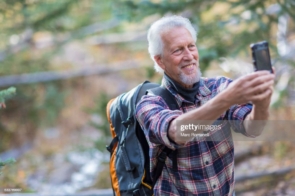 Caucasian hiker taking cell phone photograph in forest : Foto stock