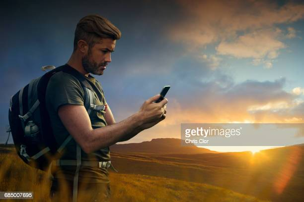 Caucasian hiker texting on cell phone at sunset