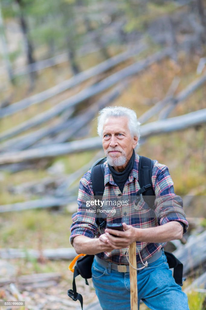 Caucasian hiker using cell phone in forest : Foto stock