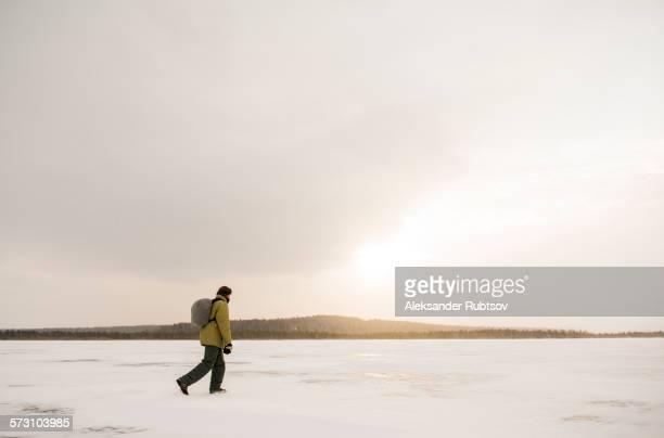 Caucasian hiker walking in snowy remote field