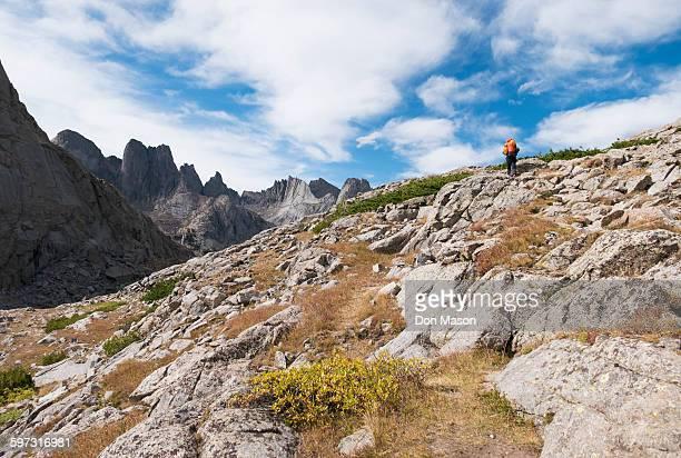 Caucasian hiker walking on rocky hillside
