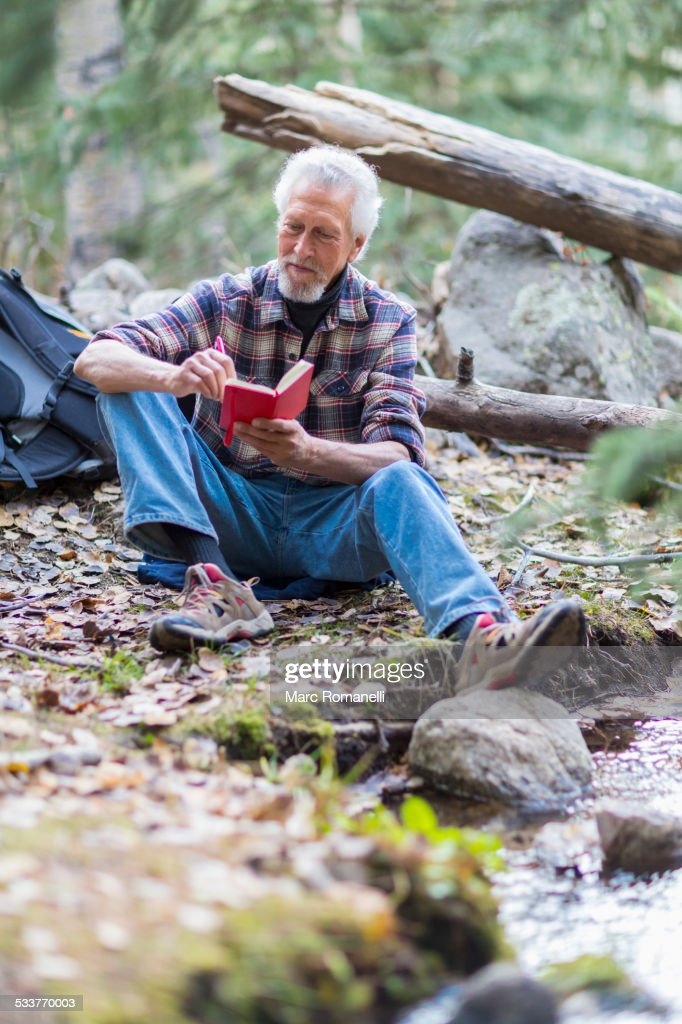 Caucasian hiker writing in forest : Foto stock