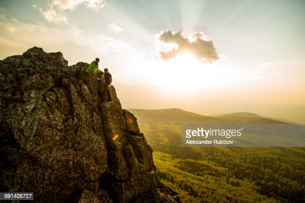 Caucasian hikers on rocky hilltop in remote landscape