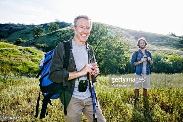 Caucasian hikers standing in grass on mountain