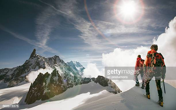 caucasian hikers standing on snowy mountain top, mont blanc, alps, france - monte bianco foto e immagini stock