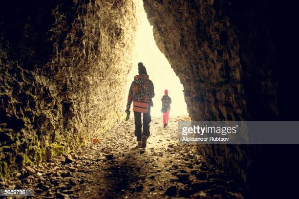 Caucasian hikers walking in rocky cave