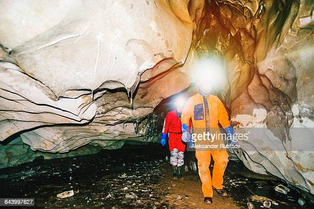 Caucasian hikers wearing headlamps in cave