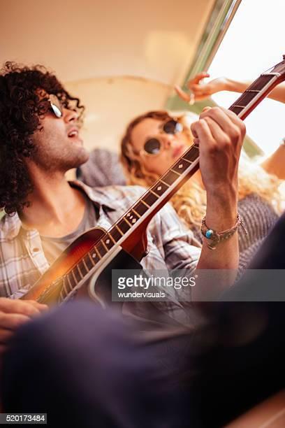 Caucasian Hipster Woman Smiles at Mixed Race Man Playing Guitar