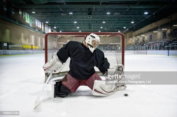 Caucasian hockey goalie blocking puck