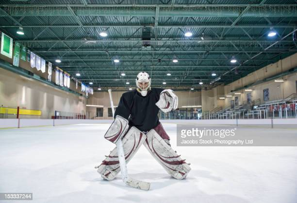 Caucasian hockey goalie standing on ice