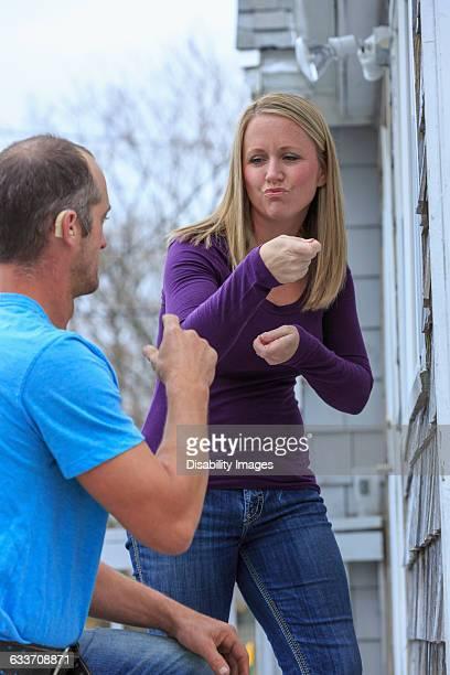 Caucasian homeowner signing to deaf repairman