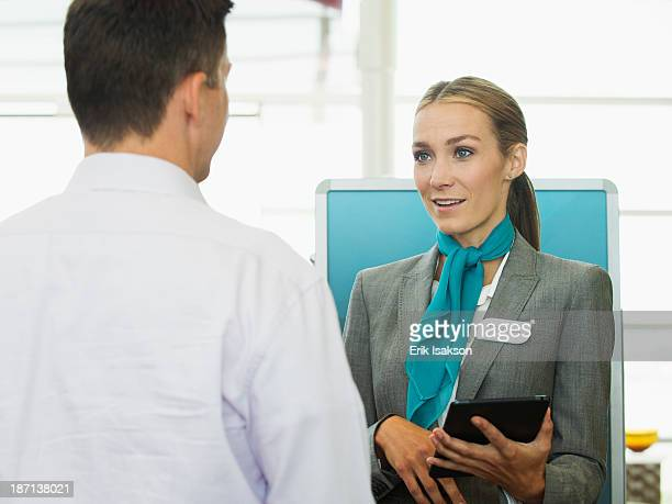 Caucasian hostess talking to businessman