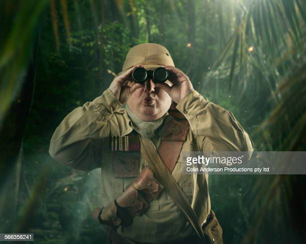 Caucasian hunter peering through binoculars in jungle