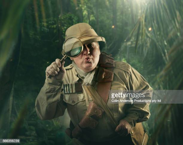 Caucasian hunter peering through magnifying glass in jungle
