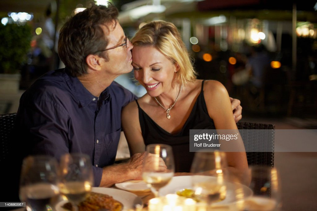 Caucasian husband kissing wife in restaurant : Stock Photo