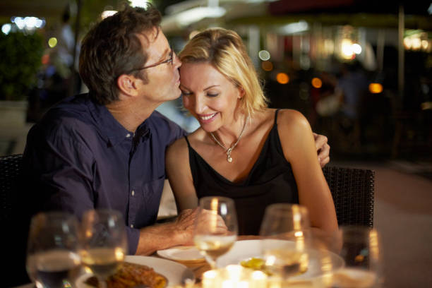 caucasian husband kissing wife in restaurant - couples romance stock pictures, royalty-free photos & images