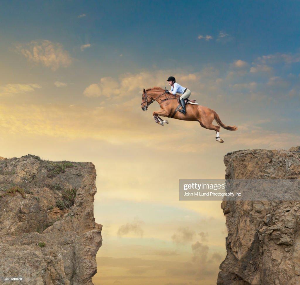Caucasian jockey jumping canyon on horse : Stock Photo