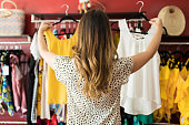Caucasian Lady Holding At Garments In Boutique