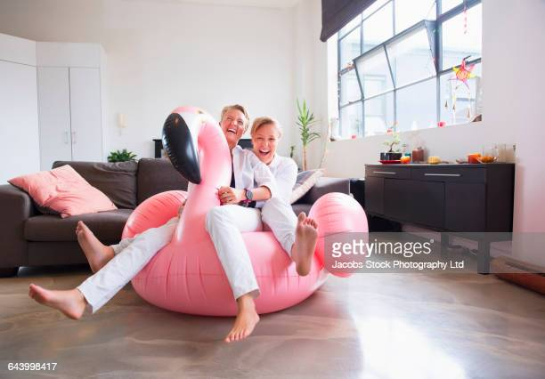 Caucasian lesbian couple sitting on inflatable flamingo