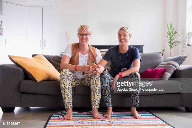 Caucasian lesbian couple smiling on sofa