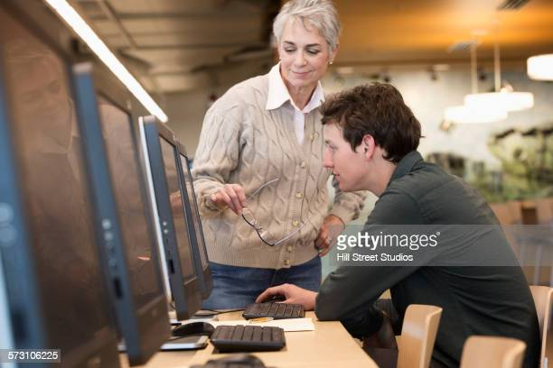 Caucasian librarian helping businessman use computer in library