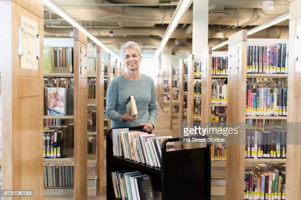 Caucasian librarian standing with book cart