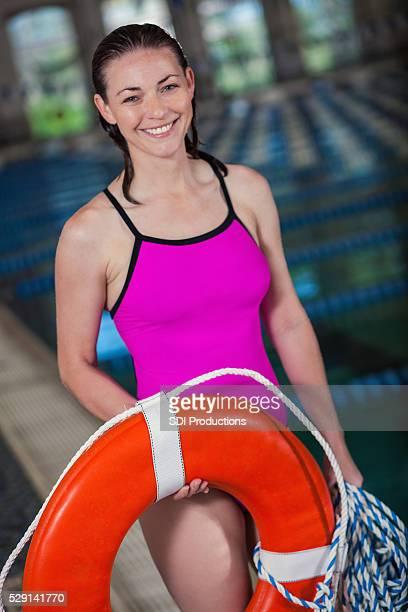 Caucasian lifeguard stands beside pool