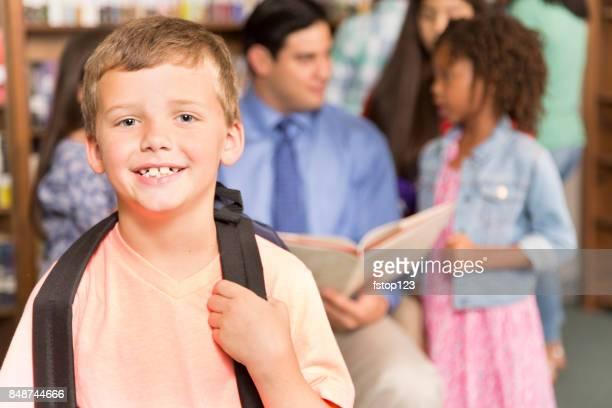 Caucasian little boy in school library.
