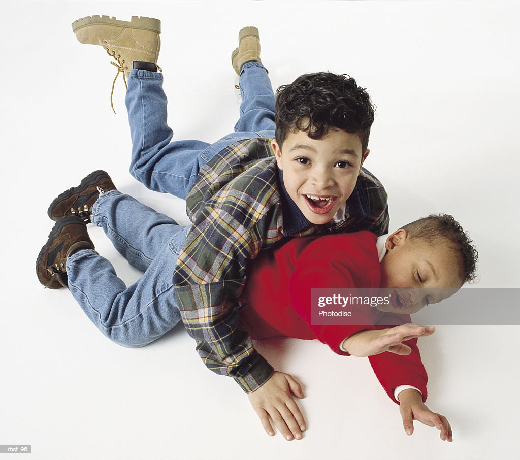 caucasian little boy tackles african american half-brother on floor with both of them laughing : Foto de stock