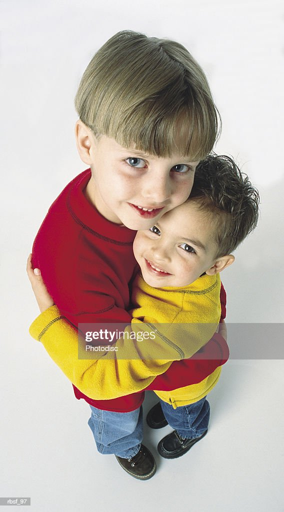 caucasian little brothers hug each other and smile wearing red and yellow shirts : Foto de stock
