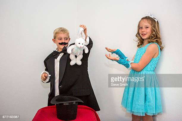 Caucasian magician pulling rabbit from hat