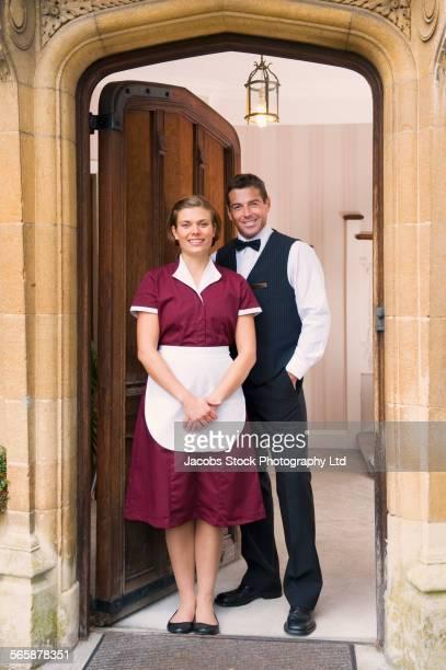 Caucasian maid and butler smiling in hotel doorway