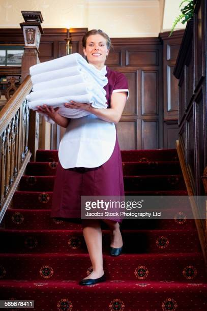 Caucasian maid carrying folded towels on hotel staircase