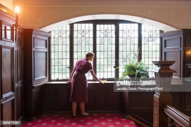Caucasian maid dusting windowsill in hotel hallway