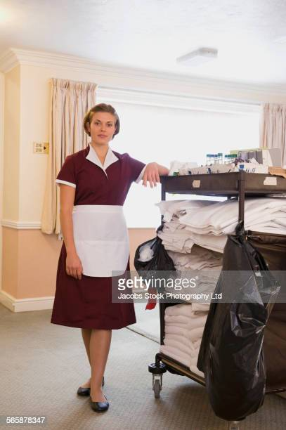 Caucasian maid with cleaning cart in hotel hallway