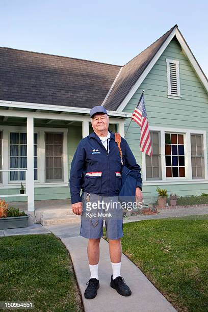 caucasian mailman standing in front yard - postal worker stock pictures, royalty-free photos & images
