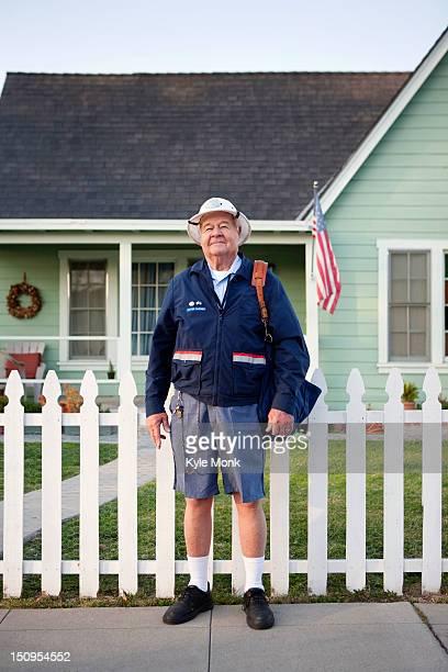 Caucasian mailman standing on sidewalk