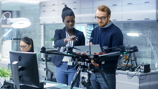 Caucasian Male and Black Female Engineers Working on a Drone Project with Help of Laptop and Taking Notes. He Works in a Bright Modern High-Tech Laboratory. 1167549771