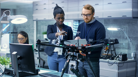 Caucasian Male and Black Female Engineers Working on a Drone Project with Help of Laptop and Taking Notes. He Works in a Bright Modern High-Tech Laboratory. 1167549790