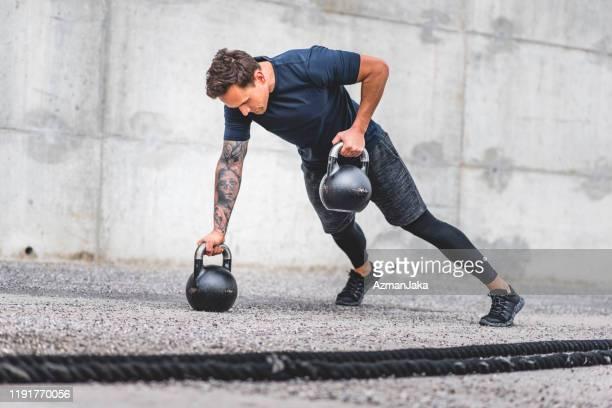 kaukasische männliche athlet doing kettlebell plank row übung - anstoß sportbegriff stock-fotos und bilder