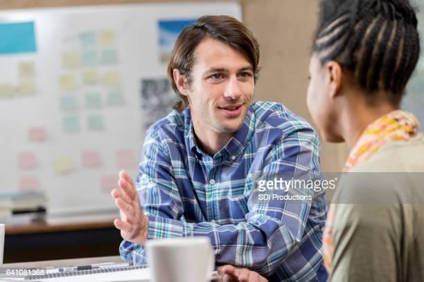 Caucasian male business professional talks with female associate
