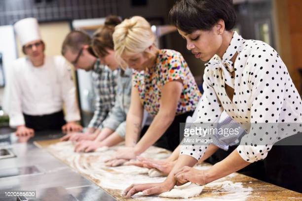 A Caucasian male chef teaching a cooking class for a mixed race group of students in a commercial kitchen,