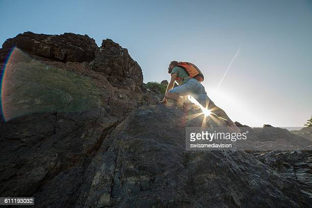 Caucasian male climbs steep rock, towards sunlight