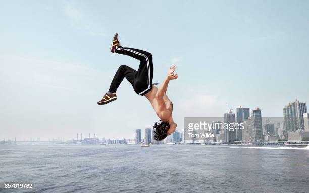 Caucasian male free running along a wall with the manhattan skyline in the background