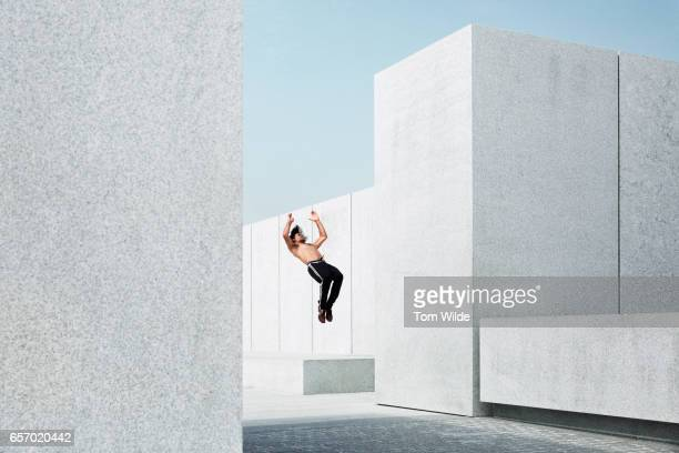 Caucasian male free running and doing a back flip in a concrete environment